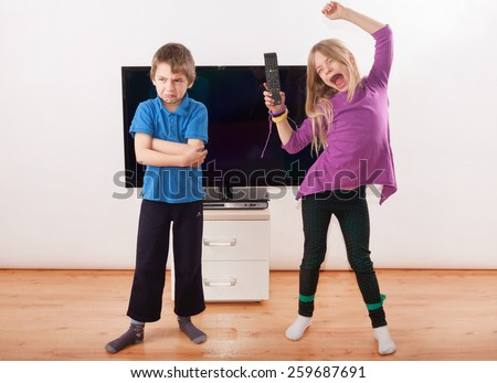 Winner in the fighting over the remote control - Sister is happy with it but her brother is very upset. - stock photo
