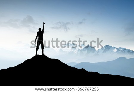 Winner silhouette on the mountain top. Sport and active life concept - stock photo