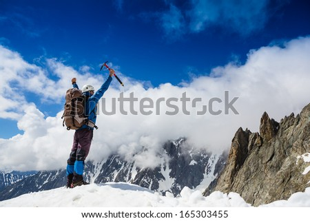 Winner / Success concept. Hiker cheering elated and blissful with arm raised in the sky after hiking to mountain top summit above the clouds  - stock photo