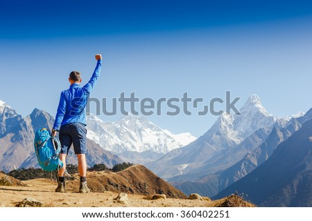 Winner / Success concept. Hiker cheering elated and blissful with arms raised in the sky after hiking. Everest base camp trek - stock photo
