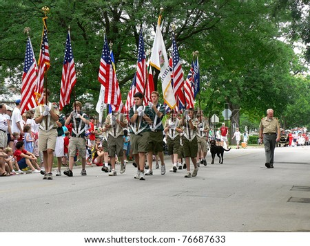 WINNETKA, ILLINOIS - JULY 4: A troop of Boy Scouts marches in a Fourth of July Parade on July 4, 2007 with unidentified spectators in the background in WINNETKA, ILLINOIS.