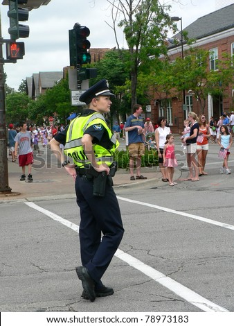 WINNETKA, ILLINOIS - JULY 4: An unidentified  female police officer watches a crowd of spectators at a Fourth of July parade on July 4, 2007 in Winnetka, Illinois.