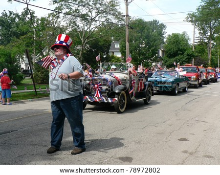 WINNETKA, ILLINOIS - JULY 4: An unidentified man marches in a Fourth of July parade with vintage cars and unidentified spectators in the background on July 4, 2008 in Winnetka, Illinois.