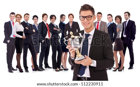 winning business team with a young man executive holding a gold trophy . happy and successful bueinssteam rewarded for it's work