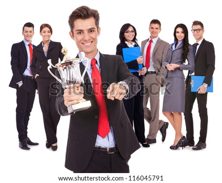 winning business team with leader holding a big trophy cup and pointing to you, on white background - stock photo
