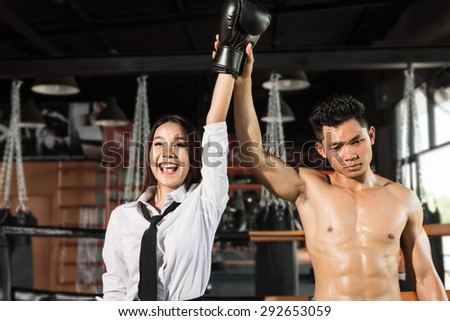 Winning business woman celebrating wearing boxing gloves and business suit on boxing ring. Winner and business success concept - stock photo