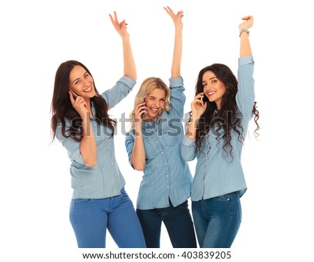 winning team of casual women talking on the phone standing with hands in the air and making the victory sign