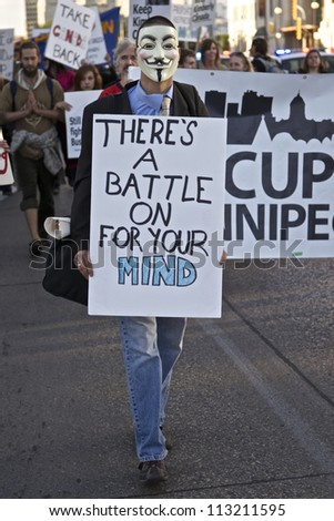 WINNIPEG, CANADA - SEPTEMBER 17: An unidentified protester wearing a Guy Fawkes mask marches with a sign in front of Occupy Winnipeg's demonstration marking of Occupy Wall Street's first anniversary. - stock photo