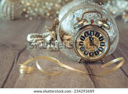 Wintage clock set on five to twelve with golden decorations. Happy New Year!