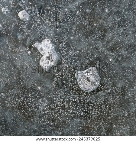Winter abstract patterns in nature: close up of air bubbles in ice on frozen lake - stock photo