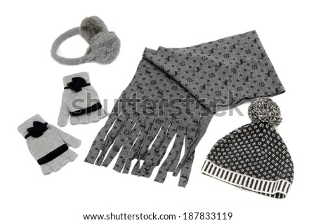 Winter accessories isolated on white background. Matching gray wool scarf, a pair of gloves, a hat and earmuffs nicely arranged.  - stock photo