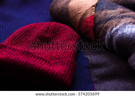 Winter accessories on the woolen plaid: scarf and red winter hat. Close up. With shallow depth of field. - stock photo