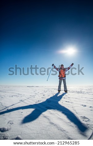 Winter adventure - young woman explorer with hands up to the sky and big shadow on snow - stock photo