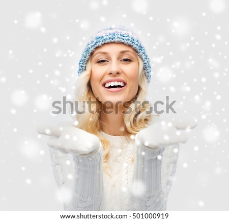 winter, advertisement, christmas and people concept - smiling young woman in winter hat and sweater holding something on her empty palms