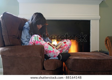 Winter Afternoon. Girl reading while curled up by the fire - stock photo