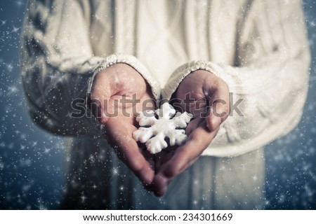 Winter and Christmas concept. Hands close-up holding a  magical snowflake - stock photo