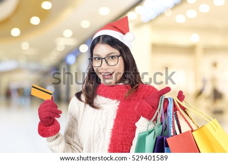 Winter and Christmas shopping concept. Woman holding a lot of gift boxes blue winter snow background. Christmas, New year, Holidays, Celebration and people with happy time.
