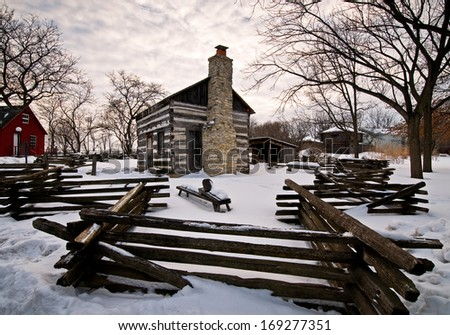 Winter at an 1843 log house at Naper Settlement in Naperville, Illinois. - stock photo