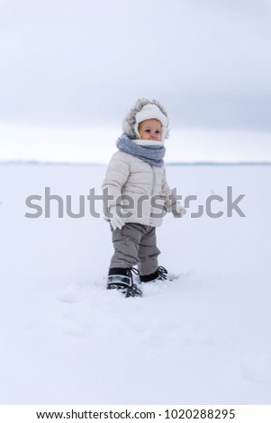Winter baby girl. Toddler kid on the snow natures. Winter clothing