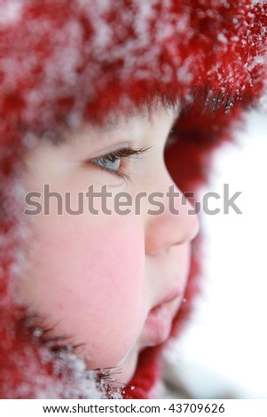 Winter baby. One year old baby dressed in warm clothing. Baby with snowflakes on his cap. - stock photo