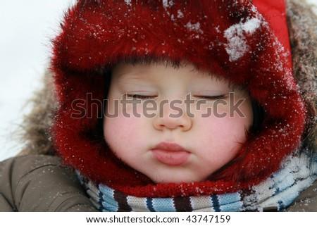 Winter baby sleeping on sled - stock photo
