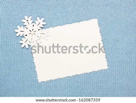 winter background: empty  blank and  snowflake on knitted fabric  - stock photo