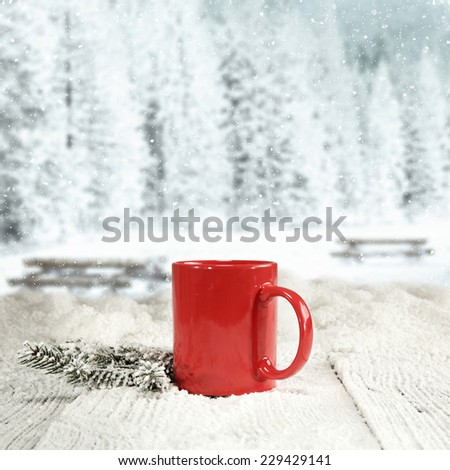 winter background of wooden old table with landscape of park in snow and red mug and green tree  - stock photo