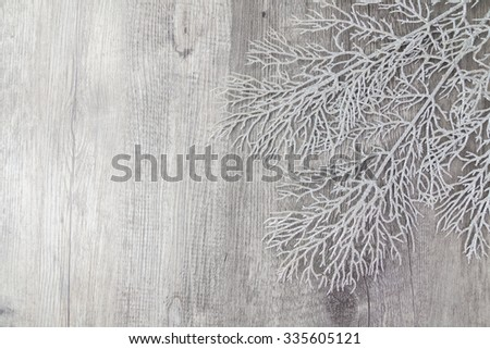 Winter background theme with silver leaf on grey wood background - stock photo