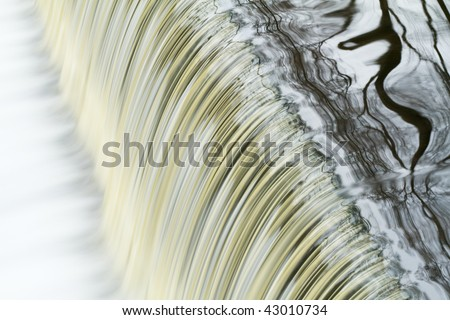 Winter, Battle Creek River cascade with abstract reflections of trees in calm water, Michigan, USA - stock photo