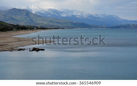 Winter Beach scape in Crete, Greece with snow on the White Mountains - stock photo