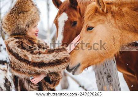 Winter beautiful Girl in  Fur Coat and hat feed the horses