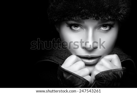 Winter Beauty Fashion. Closeup gorgeous young woman wearing trendy fur hat and mittens. Looking at camera sensually. Monochrome high fashion portrait isolated on black  with copy space. Wintry style - stock photo