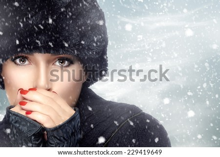 Winter beauty fashion. Lovely girl with trendy fur hat and mittens heating her hands in a snowstorm. Fashion portrait on winter background. Snowy Day. Chilling Woman in Winter Attire on Falling Snow - stock photo