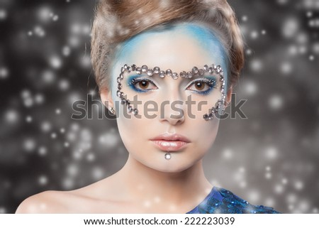 Winter Beauty Woman. Christmas Girl Makeup and Blue Dress. Holiday Make-up. Snow Queen over Gray Snow Background. - stock photo