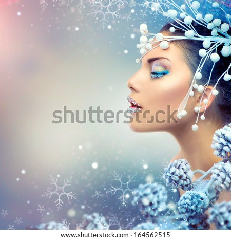 Winter Beauty Woman. Christmas Girl Makeup. Holiday Make-up. Snow Queen High Fashion Portrait over Blue Snow Background. Eyeshadows, False Eyelashes and Crystals on the Lips. Copy Space for Your Text  - stock photo