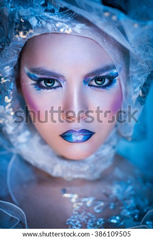Winter Beauty Woman. Christmas Girl Makeup. Holiday Make-up. Snow Queen High Fashion Portrait over Blue Snow Background. Eyeshadows, False Eyelashes and Crystals on the Lips. Copy Space for Your Tex - stock photo