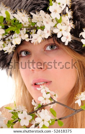 Winter beauty woman looks through spring white cherry flowers. Focus on woman's eyes. - stock photo