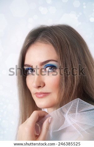 Winter beauty young woman studio portrait on blue background - stock photo