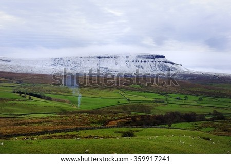 Winter Bonfire under a snow covered Pen-y-ghent - stock photo