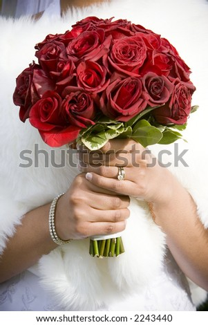 winter bride  in beautirul fur shawl holding bouquet of red roses - stock photo