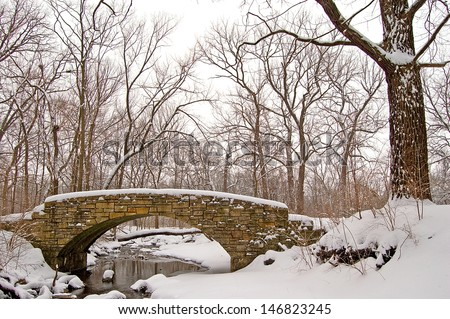 Winter Bridge Winter on a creek flowing through Black Partridge Woods Nature Preserve, Cook County, IL. - stock photo