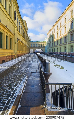 Winter Canal in Saint-Petersburg, Russia. Hermitage Bridge connecting Old Hermitage and Hermitage Theater in distance - stock photo