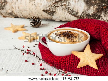 Winter cappuccino coffee in a white cup with star shaped christmas cookies and warm scarf - red and white rural still life - stock photo