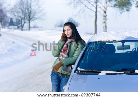 Winter car breakdown - woman call for help, road assistance - stock photo