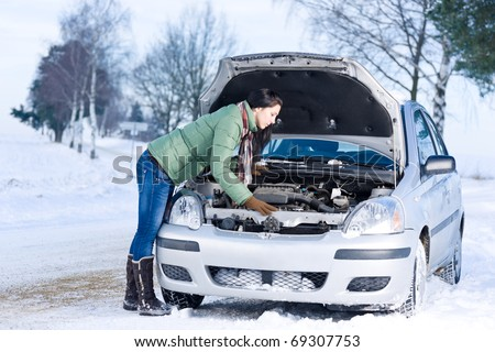 Winter car breakdown - woman try to repair motor - stock photo