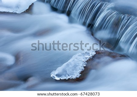 Winter cascade framed by ice, Orangeville Creek, Michigan, USA - stock photo