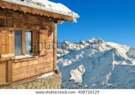 winter chalet in french alps mont blanc on blue sky background - stock photo