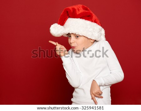 winter, child,  christmas concept - happy girl in santa hat dancing on red background - stock photo