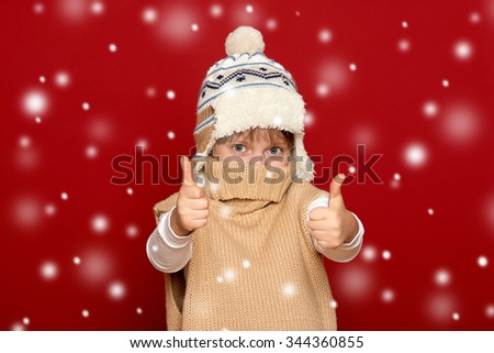 winter, child,  concept - happy girl in hat and sweater show best gesture on red background - stock photo