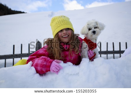 Winter, child, snow - young girl with dog enjoying winter - stock photo
